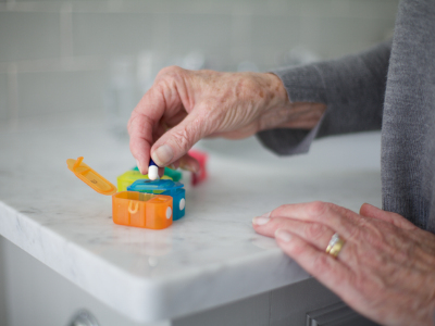 Retired women uses a Safe+Sound Health detachable seven day pillbox with push-open lids to organise her medication