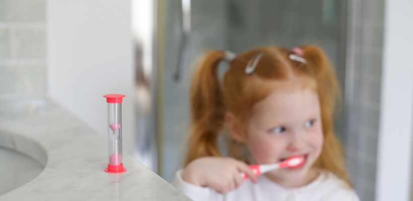 Young girl using Safe and Sound Health's children's toothbrush and two minute timer