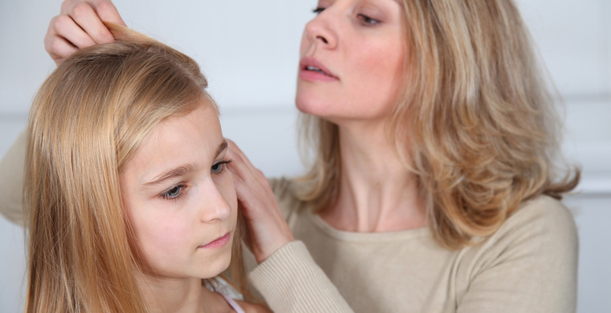 Women checks daughter hair for headlice